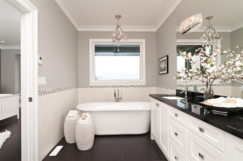 Trendy white tile black floor freestanding bathtub photo in Other with an undermount sink, recessed-panel cabinets, white cabinets and black countertops