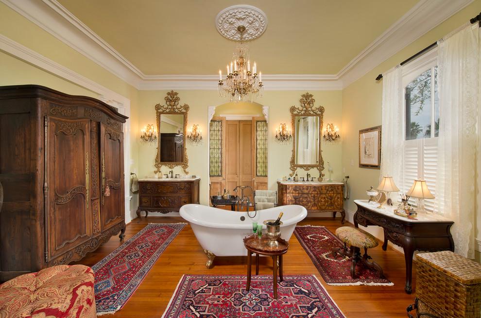Freestanding bathtub - victorian master medium tone wood floor freestanding bathtub idea in Houston with furniture-like cabinets, medium tone wood cabinets and yellow walls