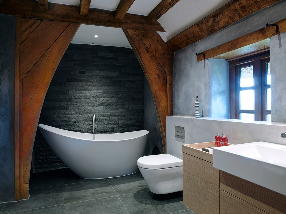 Example of a mid-sized farmhouse gray tile and stone tile porcelain tile bathroom design in Devon with a console sink, a wall-mount toilet and gray walls