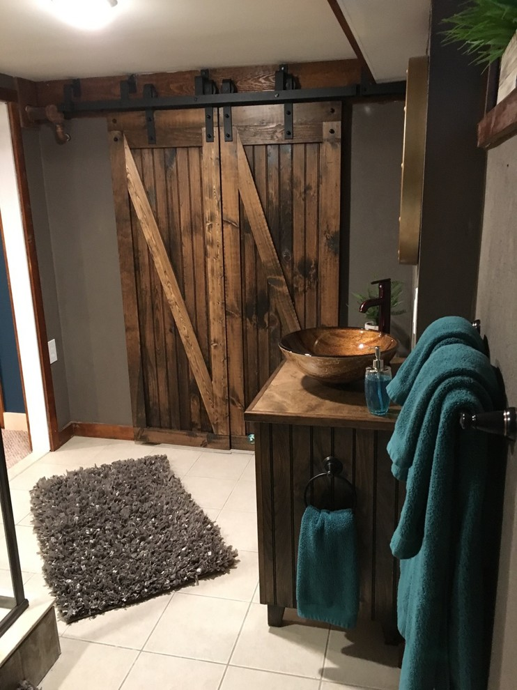 Inspiration for a small rustic multicolored tile and ceramic tile ceramic tile and beige floor corner shower remodel in Boston with beaded inset cabinets, distressed cabinets, a two-piece toilet, gray walls, a vessel sink, wood countertops and a hinged shower door