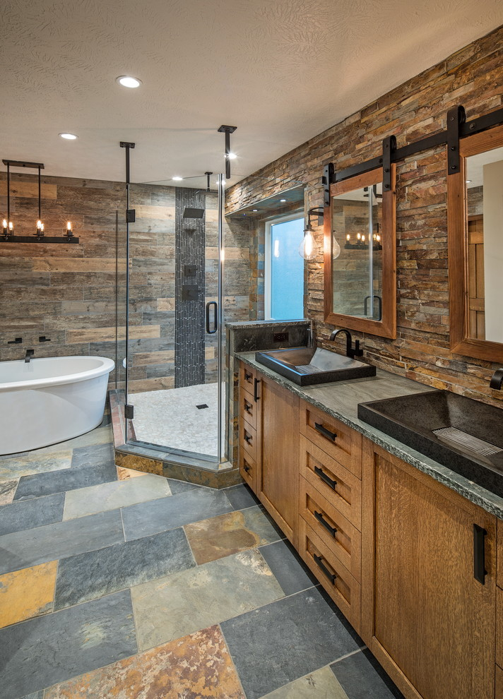 Mountain style master brown tile and stone tile bathroom photo in Omaha with shaker cabinets, medium tone wood cabinets and soapstone countertops