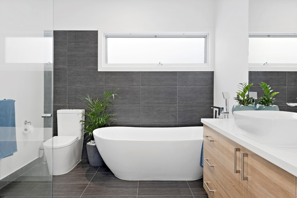 Design ideas for a beach style 3/4 bathroom in Melbourne with flat-panel cabinets, beige cabinets, a freestanding tub, a corner shower, a one-piece toilet, gray tile, white walls, a vessel sink and grey floor.