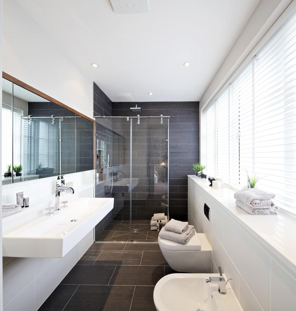 Immagine di una stanza da bagno contemporanea con doccia a filo pavimento e piastrelle grigie