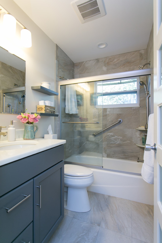 Tub/shower combo - small transitional gray tile and ceramic tile ceramic floor tub/shower combo idea in Tampa with marble countertops, an undermount sink, recessed-panel cabinets, gray cabinets, a two-piece toilet and white walls
