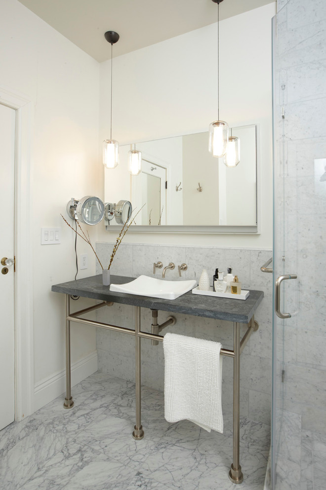 Example of a classic gray tile bathroom design in San Francisco with a console sink and soapstone countertops
