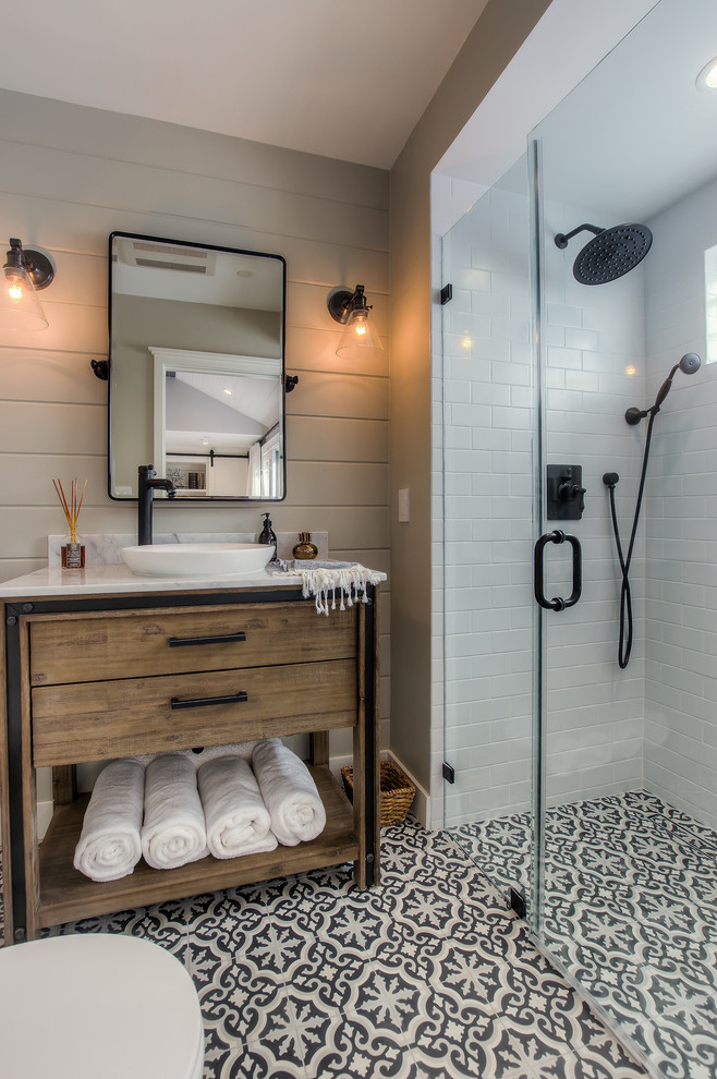Example of a transitional black and white tile cement tile floor and multicolored floor walk-in shower design in Los Angeles with furniture-like cabinets, medium tone wood cabinets, gray walls, a vessel sink and a hinged shower door