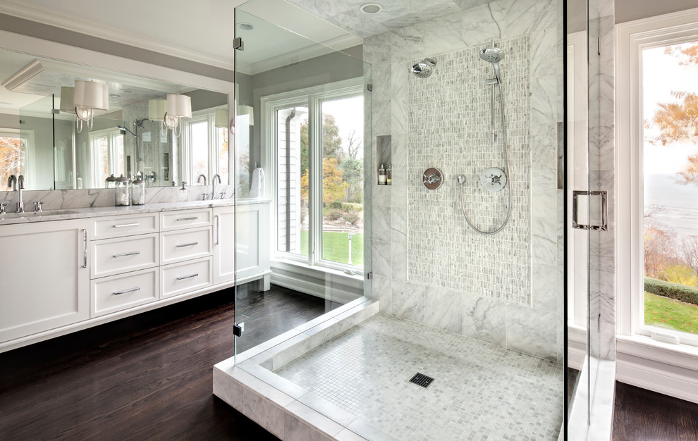 Inspiration for a transitional master white tile dark wood floor double shower remodel in Milwaukee with recessed-panel cabinets, white cabinets and gray walls