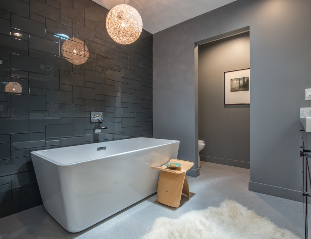 Inspiration for a mid-sized contemporary master gray tile and glass tile ceramic tile bathroom remodel in Phoenix with flat-panel cabinets, black cabinets, a one-piece toilet, gray walls, an undermount sink and quartz countertops