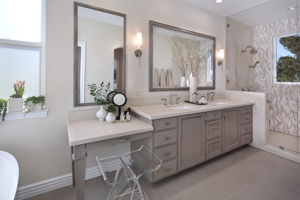 Bathroom - mid-sized transitional master stone tile beige floor and ceramic tile bathroom idea in Orange County with gray cabinets, a two-piece toilet, beige walls, quartz countertops, a hinged shower door, recessed-panel cabinets and a drop-in sink