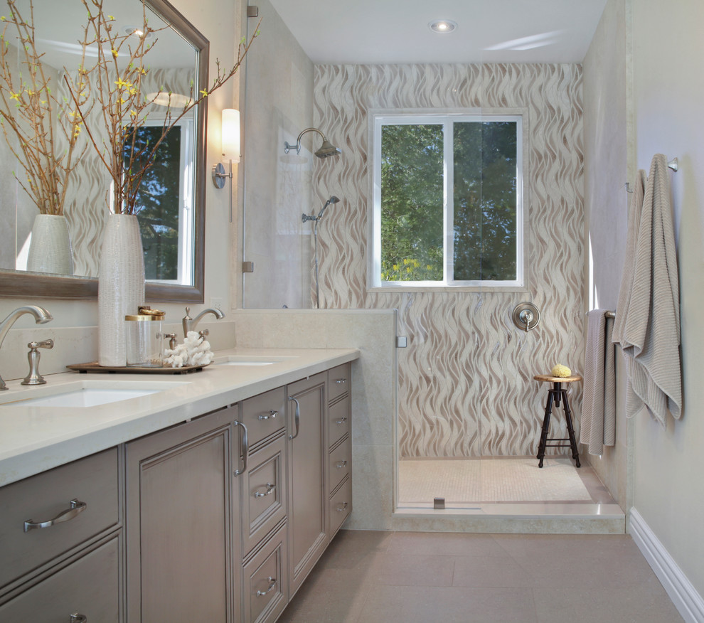 Inspiration for a mid-sized transitional master stone tile ceramic tile and beige floor bathroom remodel in Orange County with recessed-panel cabinets, gray cabinets, quartz countertops, beige walls, a drop-in sink and a hinged shower door
