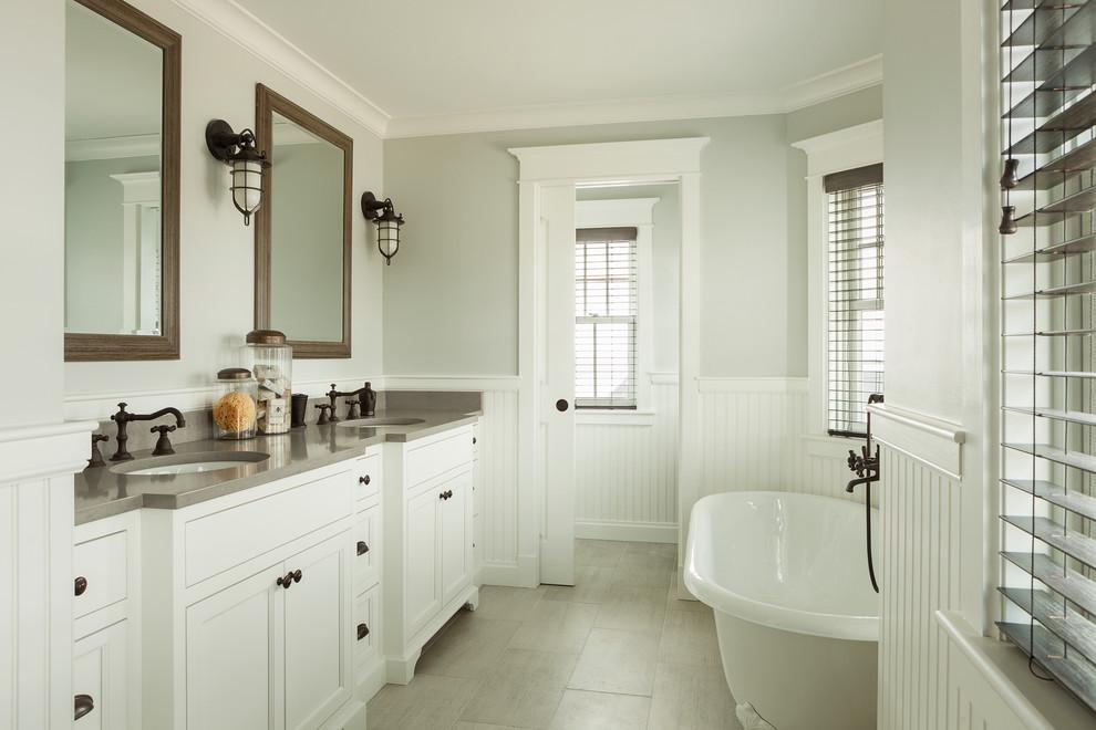 ポートランド(メイン)のビーチスタイルのおしゃれな浴室 (落し込みパネル扉のキャビネット、白いキャビネット、猫足バスタブ、グレーの壁、アンダーカウンター洗面器、グレーの床、グレーの洗面カウンター) の写真