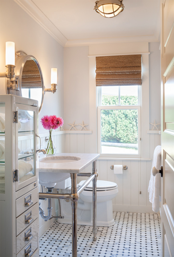 Example of a beach style bathroom design in Providence with a console sink, white cabinets and white walls