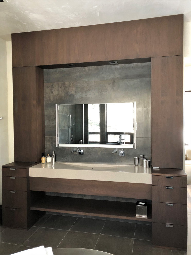 Mid-sized trendy master gray tile brown floor and double-sink bathroom photo in Other with flat-panel cabinets, dark wood cabinets, beige walls, a trough sink, a hinged shower door, beige countertops and a built-in vanity