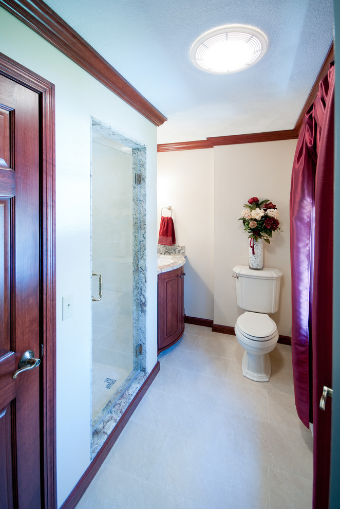 Inspiration for a mid-sized timeless master beige tile and ceramic tile porcelain tile alcove shower remodel in Providence with furniture-like cabinets, medium tone wood cabinets, granite countertops, a two-piece toilet, an undermount sink and beige walls