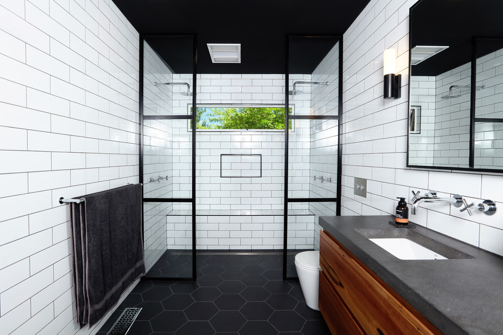 Example of a trendy master white tile and subway tile ceramic tile and black floor bathroom design in Melbourne with medium tone wood cabinets, an undermount sink, concrete countertops, flat-panel cabinets, a one-piece toilet, white walls and gray countertops