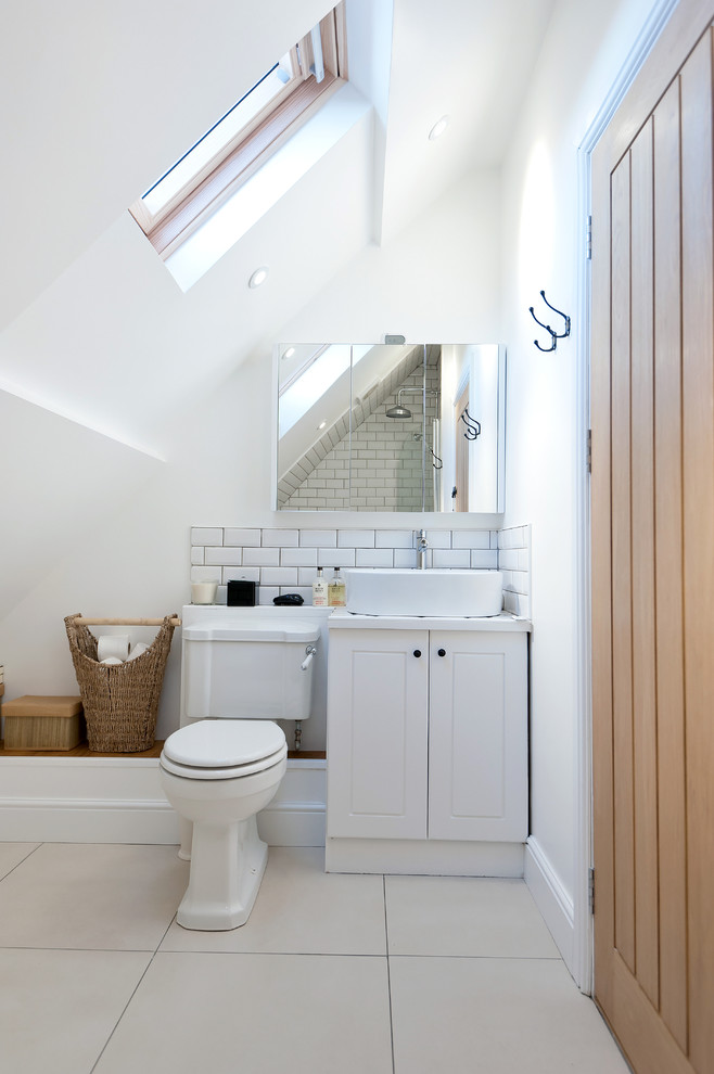 Inspiration for a cottage white tile and subway tile bathroom remodel in London with a vessel sink, white cabinets, a two-piece toilet and white walls