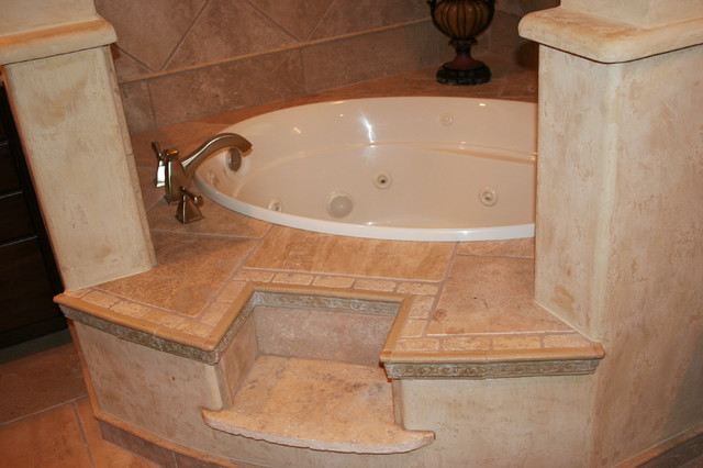 Drop-in bathtub - mid-sized mediterranean master beige tile and stone tile travertine floor drop-in bathtub idea in Austin with a drop-in sink, raised-panel cabinets, medium tone wood cabinets, a two-piece toilet and beige walls
