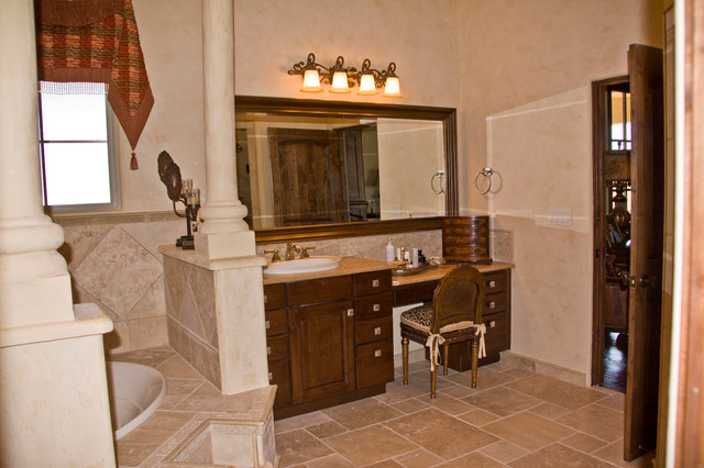 Example of a small tuscan master beige tile and stone tile travertine floor drop-in bathtub design in Austin with a drop-in sink, raised-panel cabinets, medium tone wood cabinets, a two-piece toilet and beige walls