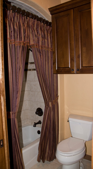 Example of a small tuscan kids' beige tile and ceramic tile tub/shower combo design in Austin with raised-panel cabinets, medium tone wood cabinets and a two-piece toilet