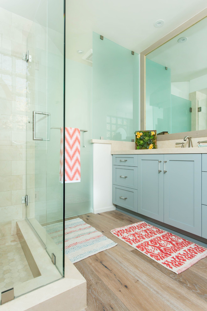 Example of a large beach style kids' beige tile and marble tile light wood floor and gray floor alcove shower design in Los Angeles with shaker cabinets, blue cabinets, a one-piece toilet, white walls, an undermount sink, marble countertops and a hinged shower door