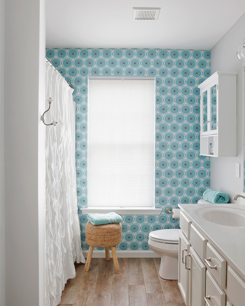 Example of a beach style beige floor bathroom design in Philadelphia with white cabinets, solid surface countertops, white countertops, raised-panel cabinets and blue walls