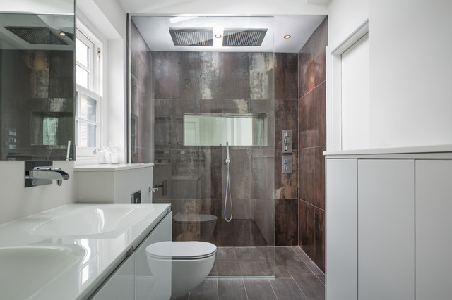 Design ideas for a large contemporary ensuite bathroom in London with flat-panel cabinets, white cabinets, a wall mounted toilet, porcelain tiles, white walls, porcelain flooring, an integrated sink, solid surface worktops and a built-in shower.