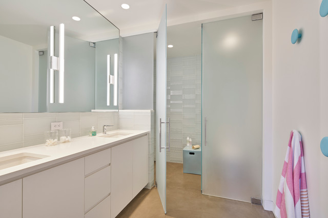 Example of a large trendy kids' white tile and glass tile concrete floor walk-in shower design in San Francisco with flat-panel cabinets, white cabinets, white walls, an undermount sink, engineered quartz countertops, a two-piece toilet and a hinged shower door