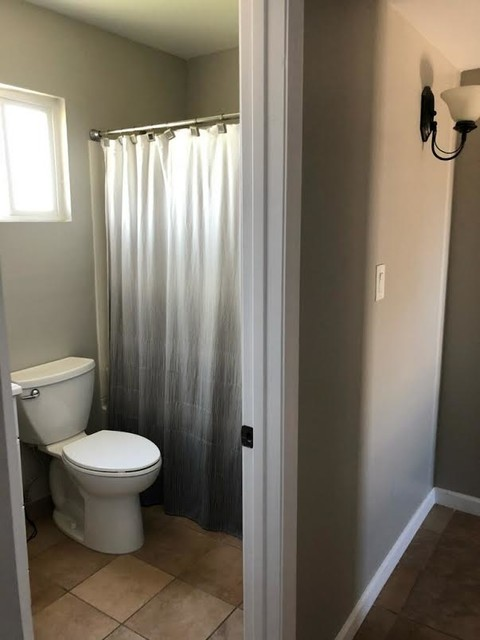 Bathroom - traditional 3/4 ceramic floor and beige floor bathroom idea in Phoenix with white cabinets, a two-piece toilet, gray walls, an undermount sink, solid surface countertops and white countertops
