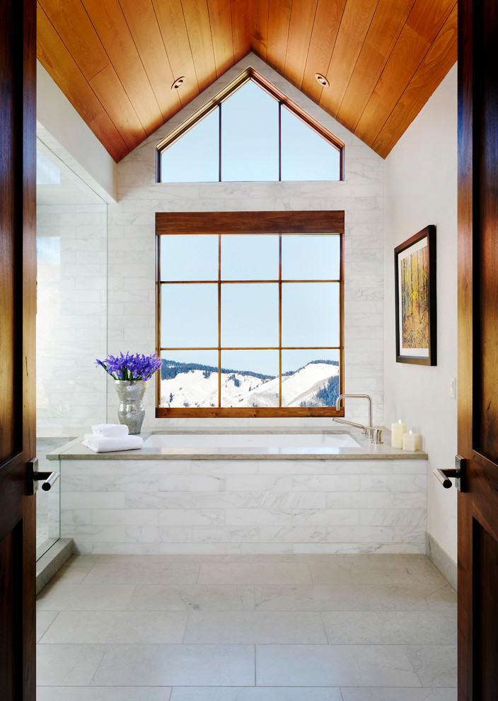 Bathroom - transitional master white tile and stone tile limestone floor bathroom idea in Denver with an undermount tub, a two-piece toilet, white walls, an undermount sink and granite countertops