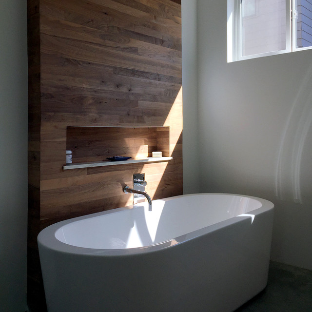 soaking tub and walnut accent wall in master bath