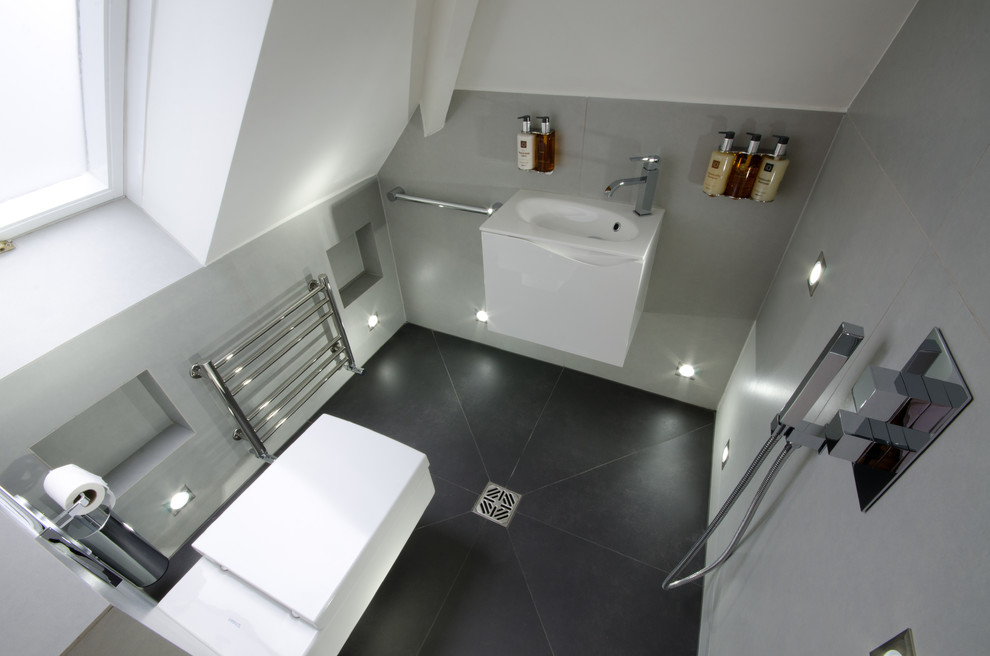 Inspiration for a small contemporary master gray tile porcelain tile doorless shower remodel in London with white cabinets, a wall-mount toilet, gray walls, a wall-mount sink and flat-panel cabinets