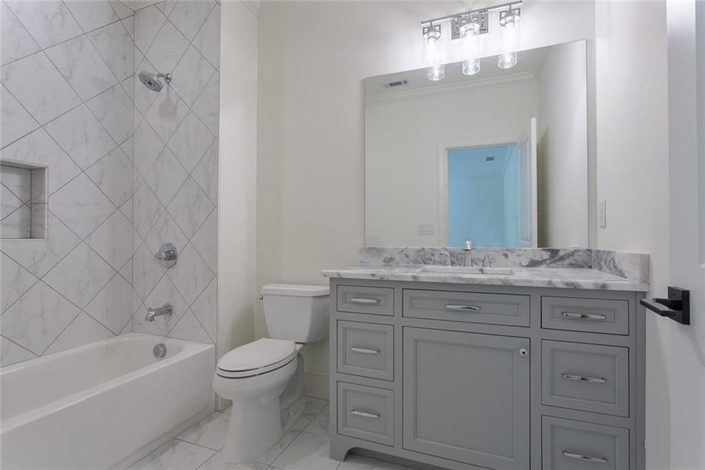 Example of a large transitional 3/4 gray tile and marble tile ceramic tile and white floor bathroom design in Atlanta with recessed-panel cabinets, gray cabinets, a two-piece toilet, white walls, an undermount sink, marble countertops and gray countertops