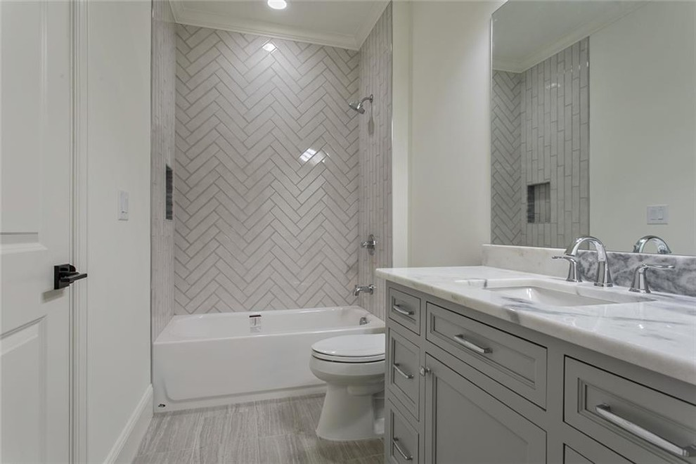 Bathroom - large transitional 3/4 gray tile and marble tile ceramic tile and gray floor bathroom idea in Atlanta with recessed-panel cabinets, gray cabinets, a two-piece toilet, white walls, an undermount sink, marble countertops and gray countertops