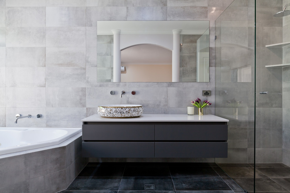 Inspiration for a mid-sized contemporary master gray tile and porcelain tile porcelain tile and gray floor walk-in shower remodel in Perth with flat-panel cabinets, gray cabinets, a one-piece toilet, gray walls, a vessel sink, quartz countertops, a hinged shower door and white countertops