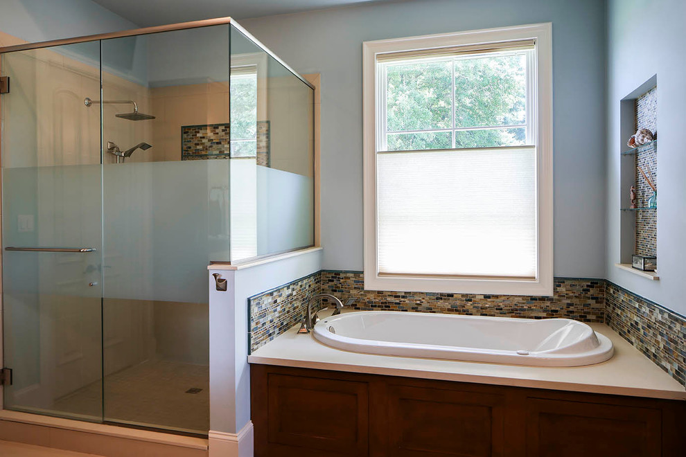 Example of a mid-sized transitional blue tile and mosaic tile porcelain floor drop-in bathtub design in New Orleans with shaker cabinets, medium tone wood cabinets, engineered quartz countertops and blue walls