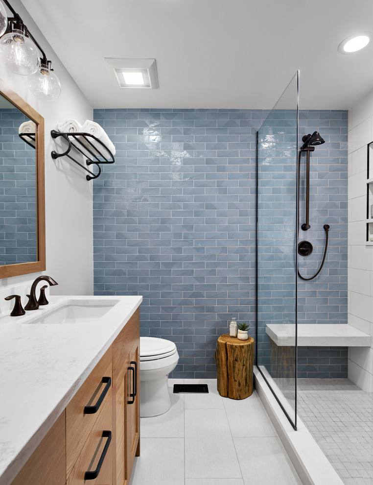 Transitional blue tile white floor bathroom photo in Chicago with light wood cabinets, white walls and white countertops