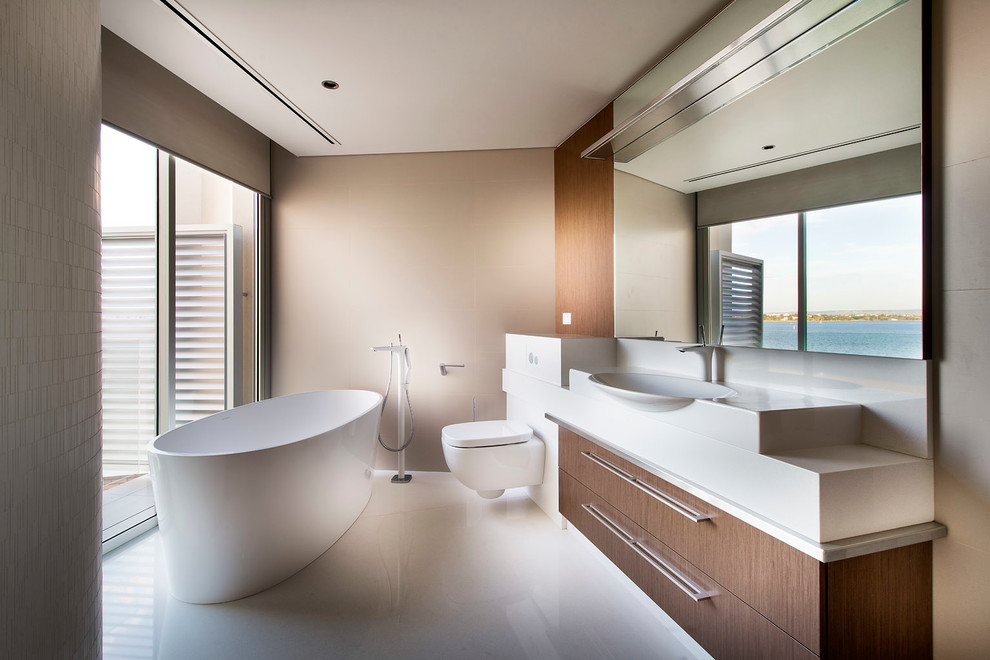 Freestanding bathtub - contemporary freestanding bathtub idea in Perth with flat-panel cabinets, a wall-mount toilet, beige walls and white countertops