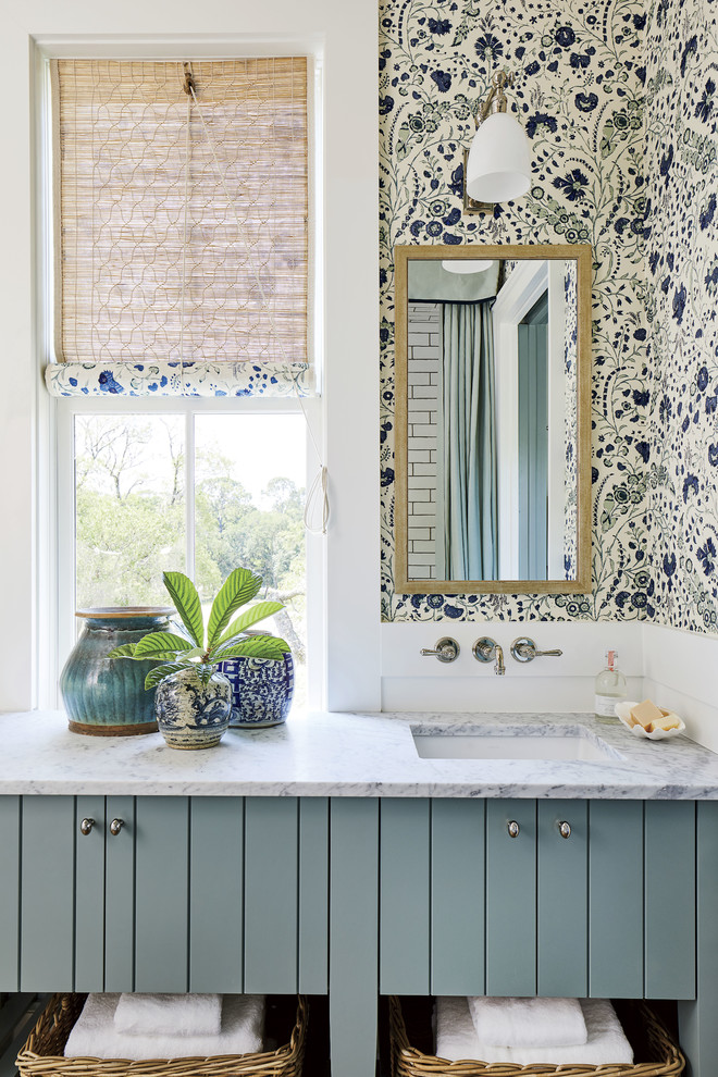 Beach style bathroom photo in Jacksonville with blue cabinets, multicolored walls, an undermount sink and white countertops