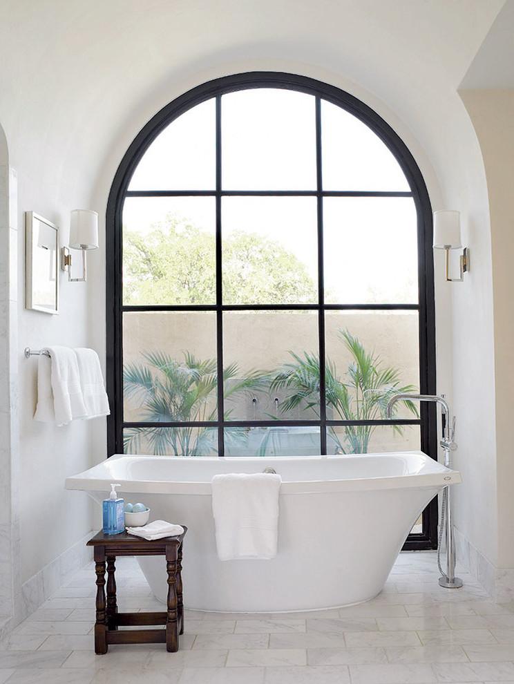 Tuscan master freestanding bathtub photo in Austin with white walls