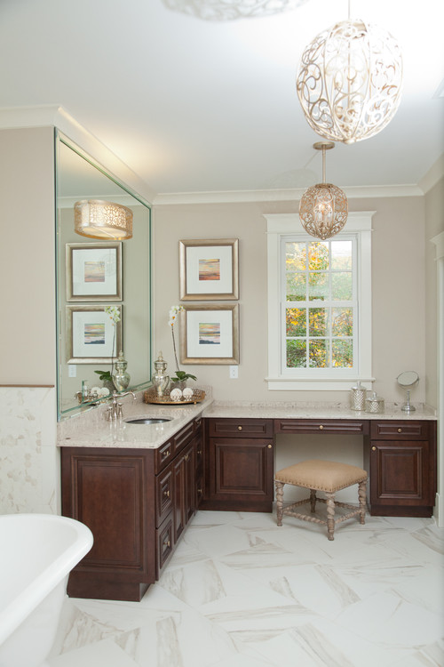 The globe-like light fixtures in this primary bathroom are a show-stopper. The intricate scroll work fits perfectly in this elegant bathroom design.
