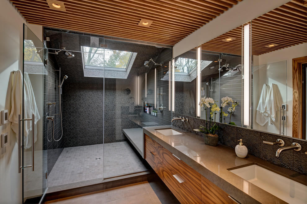 Trendy black tile gray floor and double-sink alcove shower photo in Chicago with flat-panel cabinets, medium tone wood cabinets, white walls, an undermount sink, a hinged shower door and gray countertops