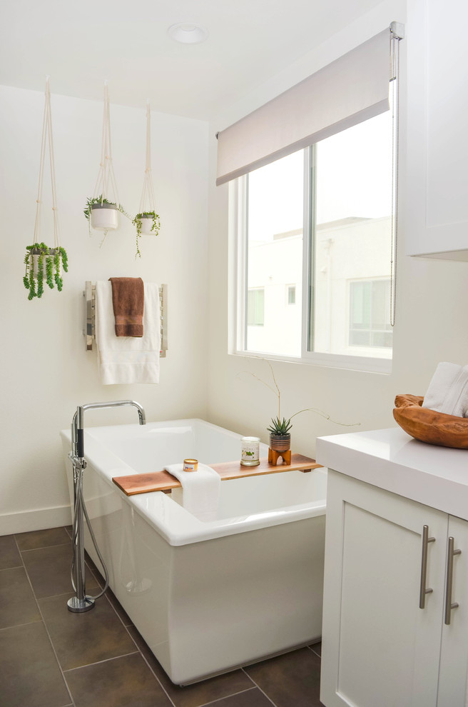 Freestanding bathtub - huge contemporary master porcelain tile and brown floor freestanding bathtub idea in Los Angeles with shaker cabinets, white cabinets, white walls, solid surface countertops and white countertops