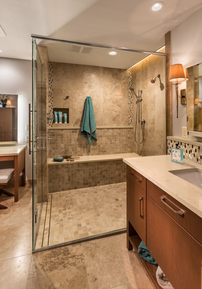 Example of a large trendy master beige tile and marble tile marble floor and beige floor walk-in shower design in Milwaukee with an undermount sink, flat-panel cabinets, medium tone wood cabinets, quartz countertops, a one-piece toilet, gray walls and a hinged shower door
