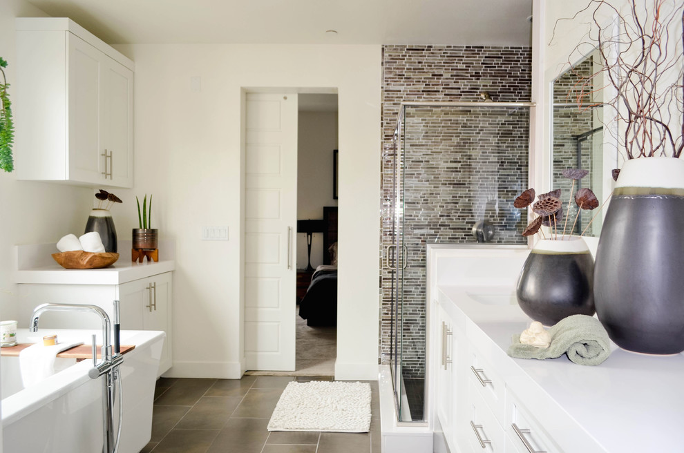 Huge transitional master gray tile and glass sheet porcelain tile and gray floor bathroom photo in Los Angeles with shaker cabinets, white cabinets, a one-piece toilet, white walls, an undermount sink, solid surface countertops, a hinged shower door and white countertops