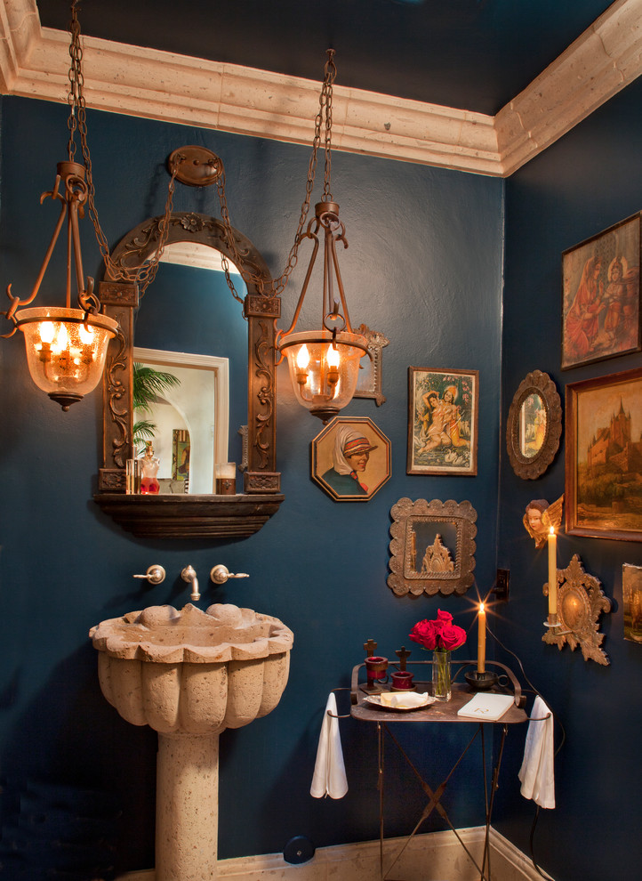 Example of a tuscan bathroom design in Phoenix with a pedestal sink and blue walls
