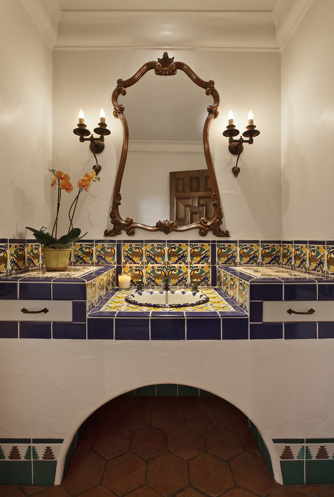 Bathroom - mediterranean multicolored tile and ceramic tile terra-cotta tile bathroom idea in Santa Barbara with a drop-in sink, tile countertops and white walls