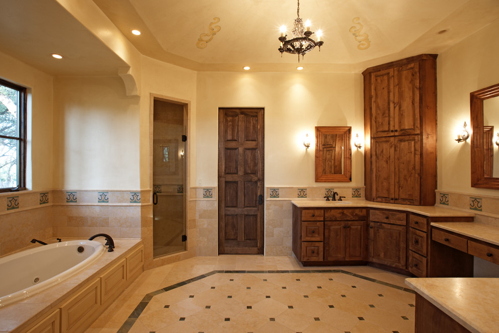 Inspiration for a mediterranean beige tile bathroom remodel in Austin with raised-panel cabinets and dark wood cabinets