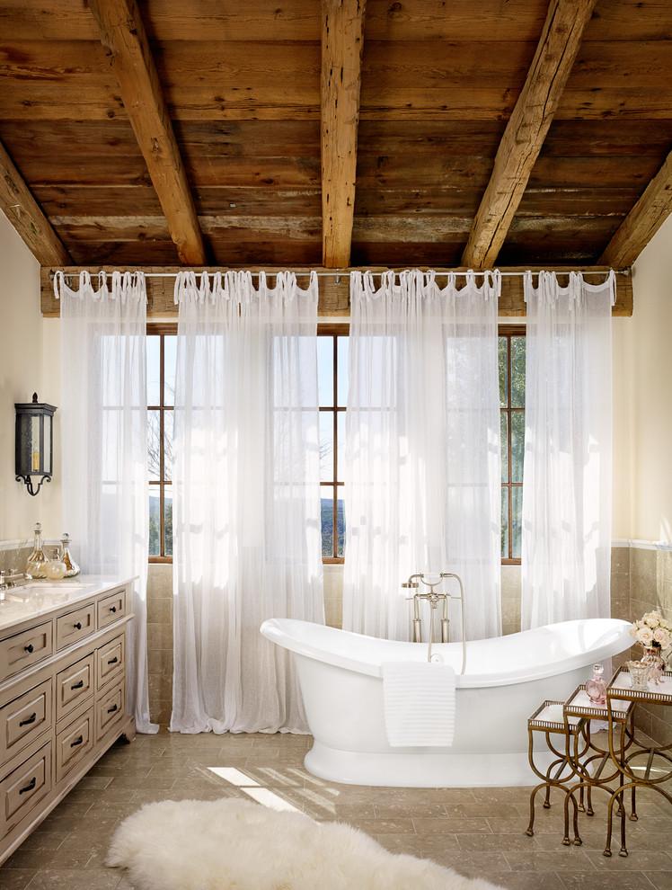 Idee per una stanza da bagno mediterranea con ante grigie, vasca freestanding, piastrelle grigie, pareti bianche e lavabo sottopiano