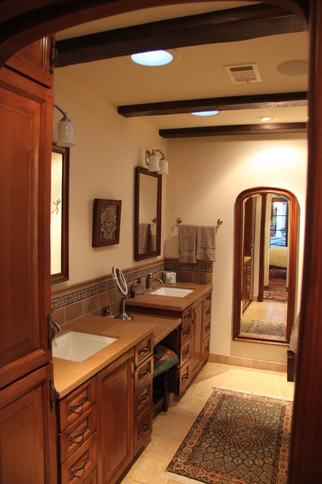 Mid-sized tuscan master beige tile and stone tile alcove shower photo in Denver with an undermount sink, raised-panel cabinets, medium tone wood cabinets, limestone countertops, a two-piece toilet and beige walls