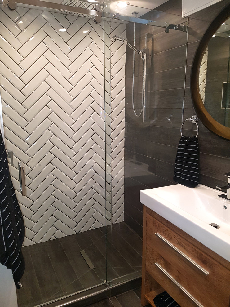 Bathroom - mid-sized modern black tile and ceramic tile porcelain tile and black floor bathroom idea in Toronto with furniture-like cabinets, brown cabinets, a two-piece toilet, white walls, a vessel sink, solid surface countertops and white countertops